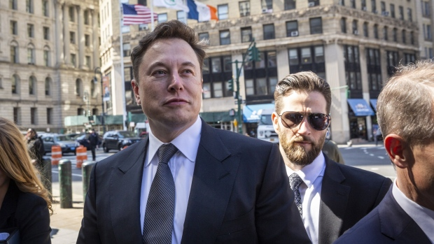 Elon Musk, chief executive officer of Tesla Inc., left, arrives at federal court in New York, U.S., on Thursday, April 4, 2019.