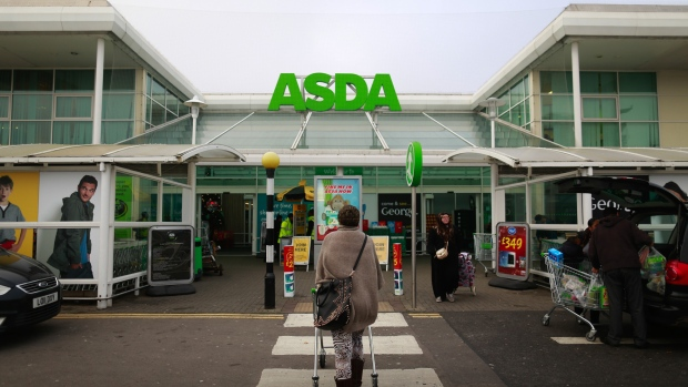 A customer pushes a shopping cart as she walks towards an Asda supermarket, operated by Wal-Mart Stores Inc., in the Wembley district of London, U.K.
