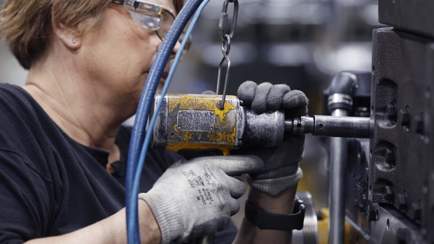 A factory worker uses a power drill to assemble components on a diesel engine in Seymour, Indiana.