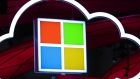Microsoft Corp. logo, center, hang beside an illuminated iCloud icon at the CeBIT 2017 tech fair in Hannover, Germany.