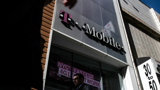 Pedestrians pass in front of a T-Mobile US Inc. store in New York, U.S. on Monday, April 30, 2018. Sprint Corp. suffered its worst stock decline in almost six months, rocked by fears that a proposed $26.5 billion takeover by T-Mobile US Inc. will get rejected by antitrust enforcers.