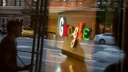 Pedestrians are reflected in a window looking into a lobby of the Google Inc. offices in New York.