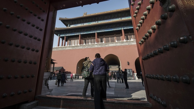 Visitors walk through a gate inside the Palace Museum at the Forbidden City in Beijing,