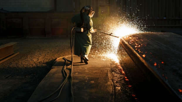 Sparks fly as an employee performs a quality check on a steel slab at a plant in Nanticoke, Ontario, Canada.