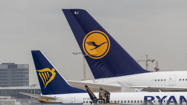 Passenger aircraft, operated by Ryanair Holdings Plc, left, and Deutsche Lufthansa AG, sit on tarmac beyond the construction site of Frankfurt airport's new Terminal 3 in Frankfurt, Germany, on Monday, April 29, 2019.