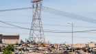 A pylon tower carries electrical power lines over residential shacks, some equipped with solar power geysers on their roofs, in the Alexandra township outside Johannesburg, South Africa, on Thursday, Oct. 6, 2016.