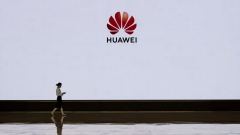 SHENZHEN, CHINA - APRIL 12: A member of Huawei's reception staff walks in front of a large screen displaying the logo in the foyer of a building used for high profile customer visits and displays at the company's Bantian campus on April 12, 2019 in Shenzhen, China. Huawei is Chinas most valuable technology brand, and sells more telecommunications equipment than any other company in the world, with annual revenue topping $100 billion U.S. Headquartered in the southern city of Shenzhen, considered Chinas Silicon Valley, Huawei has more than 180,000 employees worldwide, with nearly half of them engaged in research and development. In 2018, the company overtook Apple Inc. as the second largest manufacturer of smartphones in the world behind Samsung Electronics, a milestone that has made Huawei a source of national pride in China. While commercially successful and a dominant player in 5G, or fifth-generation networking technology, Huawei has faced political headwinds and allegations that its equipment includes so-called backdoors that the U.S. government perceives as a national security. U.S. authorities are also seeking the extradition of Huaweis Chief Financial Officer, Meng Wanzhou, to stand trial in the U.S. on fraud charges. Meng is currently under house arrest in Canada, though Huawei maintains the U.S. case against her is purely political. Despite the U.S. campaign against the company, Huawei is determined to lead the global charge toward adopting 5G wireless networks. It has hired experts from foreign rivals, and invested heavily in R&D to patent key technologies to boost Chinese influence. (Photo by Kevin Frayer/Getty Images)