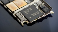 A Qualcomm Inc. baseband modem integrated circuit (IC) chip, center, of an Apple Inc. iPhone 6 smartphone is seen in an arranged photograph in Bangkok, Thailand, on Saturday, Feb. 3, 2018. Apple Chief Executive Officer Tim Cook told shareholders on Feb. 13 at the company's annual meeting to expect higher dividends and stressed that succession planning is a priority.