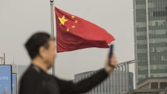 A Chinese national flag flies as a man uses a smartphone in Shanghai, China, on Tuesday, Nov. 27, 2018. Apple, which has lost a fifth of its value in a tech market rout since October, is poised for another setback after U.S. President Donald Trump suggested that 10 percent tariffs could be placed on mobile phones, like the iPhone, and laptops made in China.