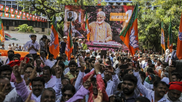 India election 2019: Supporters celebrate in front of a banner featuring Narendra Modi