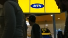 Shoppers pass the entrance to an MTN Group Ltd. telecommunications store at the Clearwater Mall in Johannesburg, South Africa, on Thursday, Aug. 3. 2017. MTN Group Ltd.said a Nigerian listing that it agreed to as part of a $1 billion regulatory fine was on track and would take place within the next six to 12 months.