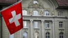 "A Swiss national flag hangs in view of the Swiss National Bank (SNB) in Bern, Switzerland, on Friday, April 26, 2019. The Swiss National Bank is in no position to raise interest rates given markets are still in a ""fragile"" state, according to President Thomas Jordan."