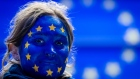 A woman wearing face paint in a EU flag design follows results of the European Parliament elections