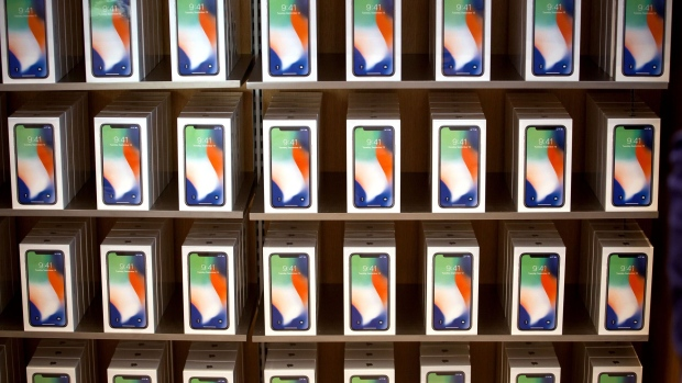 Apple Inc. iPhone X smartphones are displayed during the sales launch at a store in New York, U.S., on Friday, Nov. 3, 2017. The $1,000 price tag on Apple Inc.'s new iPhone X didn't deter throngs of enthusiasts around the world who waited -- sometimes overnight -- in long lines with no guarantee they would walk out of the store with one of the coveted devices.