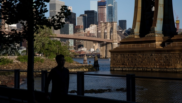 A pedestrian walks along the waterfront in Main Street Park in the Brooklyn borough of New York, U.S., on Wednesday, May 22, 2019. Stocks slumped globally on Thursday and traders took refuge in gold and bonds as the simmering trade dispute between the world's two largest economies took a greater toll on markets.