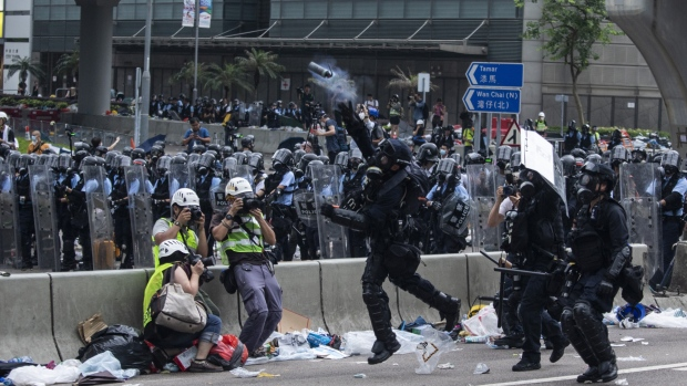 A riot police member throws a tear gas canister towards protesters on June 12. Photographer: Justin Chin/Bloomberg