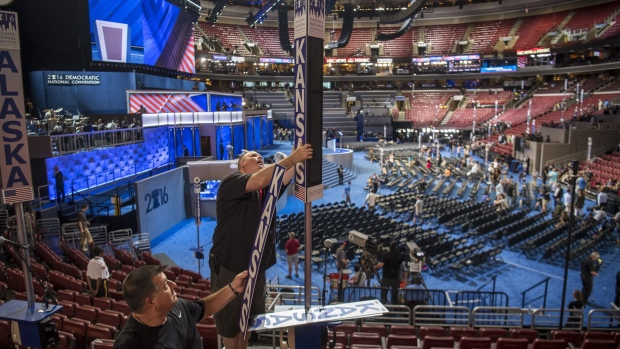 Workers attach a Kansas state sign to a pole inside the Wells Fargo Center ahead of the Democratic National Convention (DNC) in Philadelphia, U.S., on Sunday, July 24, 2016. A heat wave has settled over the City of Brotherly Love as tens of thousands of delegates converge on the city for the Democratic National Convention. Photographer: David Paul Morris/Bloomberg