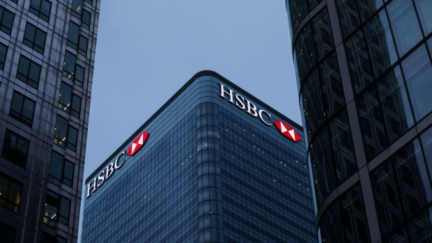 Logos sit illuminated on the HSBC Holdings Plc headquarter skyscraper offices in the Canary Wharf business, financial and shopping district in London.