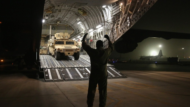 An airman guides a Humvee down a U.S. Air Force C-17 Globemaster cargo jet on January 9, 2016 at a base in an undisclosed location in the Persian Gulf Region.