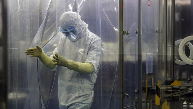 An employee in protective clothing exits an area of a research and development in Bengaluru, India.