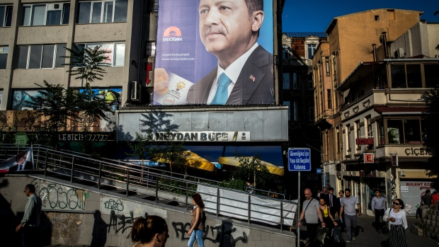 ISTANBUL, TURKEY - JUNE 18: People walk past election posters showing the portrait of Turkey's President Recep Tayyip Erdogan on June 19, 2018 in Istanbul, Turkey. Presidential candidates from all parties are holding campaign rallies across Turkey a week ahead of the countries June 24, parliamentary and presidential elections. (Photo by Chris McGrath/Getty Images)