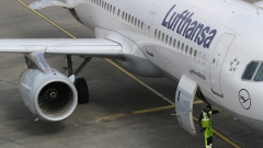 A ground crew member stands beneath an Airbus A321 aircraft, operated by Deutsche Lufthansa AG, at Tegel airport in Berlin, Germany, on Wednesday, March 13, 2019. Boeing Co. staggered into a deepening global crisis as governments around the world grounded the company's best-selling jet over safety concerns after a second deadly crash.