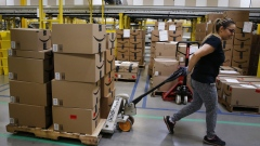 An employee pulls a cart stacked with boxes at the Amazon.com fulfillment center in Kenosha, Wisconsin, U.S., on Tuesday, Aug. 1, 2017. Amazon.com Inc. held a giant job fair at nearly a dozen U.S. warehouses as part of its effort to hire 100,000 people in the U.S. by 2018.