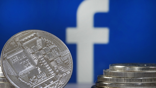 "In this photo illustration, a visual representation of a digital cryptocurrency coin sits on display in front of a Facebook logo on June 17, 2019 in Paris, France. Facebook will announce Tuesday, June 18 the details of its cryptocurrency, called ""Libra"". Like bitcoin, the best-known virtual currency, it will rely on blockchain technology."