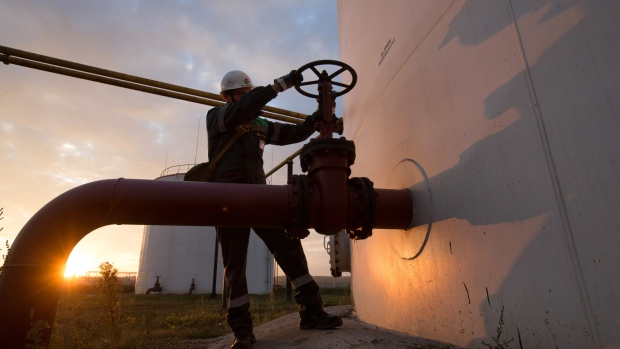 An employee turns a control valve on pipework beside a storage tank at an oil delivery point operated by bashneft pao in sergeevka village near ufa russia on monday sept 26 2016 bashneft distributes petroleum products and petrochemicals around the world and in russia via filling stations