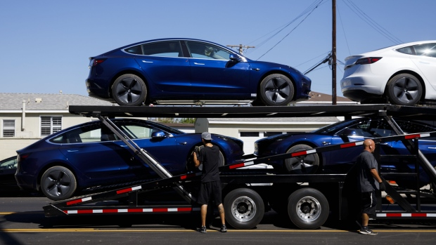 Workers unload Tesla Inc. Model 3 electric vehicles from a car carrier outside the company's delivery center in Marina Del Rey, California, U.S., on Saturday, Sept. 29, 2018. Tesla brought the total number of Model 3 produced in the third quarter to over 51,000 vehicles.