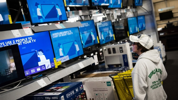 A shopper looks at televisions displayed for sale.