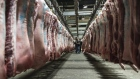 Buyers inspect pig carcasses hanging from a conveyor at a pork wholesale market, Shanghai