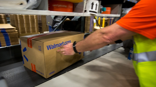 An employee places a package on a conveyor belt inside a Wal-Mart Stores Inc. fulfillment center in Bethlehem, Pennsylvania, U.S., on Wednesday, March 29, 2017.