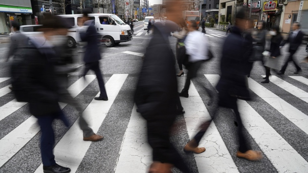 Pedestrians cross a road in Tokyo's business district, Japan, on Friday, March 29, 2019. The Bank of Japan (BOJ) will release its quarterly Tankan business sentiment survey on April 1.