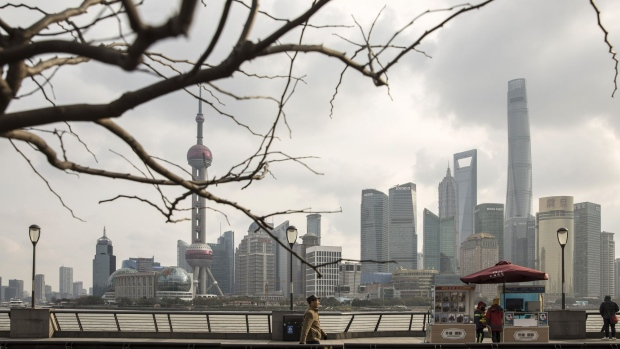 Pedestrians walk along the Bund as skyscrapers of the Pudong Lujiazui Financial District stand across the Huangpu River in Shanghai, China, on Friday, Dec. 28, 2018. China announced plans to rein in the expansion of lending by the nation's regional banks to areas beyond their home bases, the latest step policy makers have taken to defend against financial risk in the world's second-biggest economy.