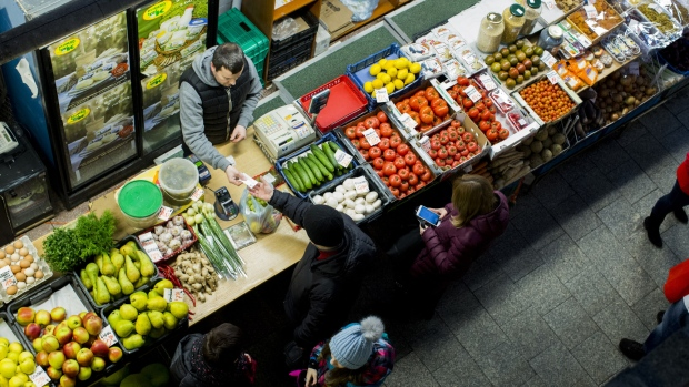 A customer pays for goods bought from a vegetable and fruit stall at an indoor market in Wroclaw, Poland, on Monday, Feb. 6, 2017. Poland's economy expanded at the weakest pace in three years as investments dropped after a change of government ushered in the biggest political shifts in the country since the collapse of communism more than a quarter century ago.