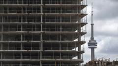 The CN Tower stands behind a condominium building under construction in downtown Toronto, Ontario, Canada, on Thursday, May 10, 2018. The dollar value of building permits for multiple-unit homes exceeded single-unit properties for the first time on a quarterly basis between January and March.