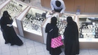 Female shoppers wearing traditional Saudi Arabian dress browse watches on sale at a luxury concession stand inside the Kingdom Centre shopping mall in Riyadh, Saudi Arabia.