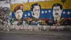 A pedestrian passes in front of a mural depicting the late Hugo Chavez, Simon Bolivar, and Nicolas Maduro, Venezuela's president, in the Palo Verde neighborhood of Caracas.