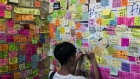 A pedestrian writes a note as messages are posted on a Lennon Wall in Hong Kong