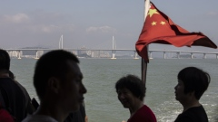 A Chinese flag flies on a boat as the Hong Kong-Zhuhai-Macau Bridge stands in the distance in Zhuhai