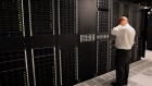 A public relations employee looks over racks of servers inside pod one of International Business Machines Corp.'s (IBM) Softlayer data center in Dallas.