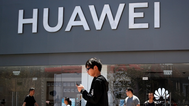 People walk past a Huawei retail store in Beijing, Sunday, June 30, 2019.