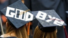"Two graduates display a farewell message on their mortarboards during Syracuse University's commencement ceremony at the Carrier Dome in Syracuse, New York, U.S., on Sunday, May 16, 2010. Students entering one of the weakest job markets in history need to have the courage to speak the truth, ""even when it's unpopular,"" JPMorgan Chase & Co. Chief Executive Officer Jamie Dimon told graduates."