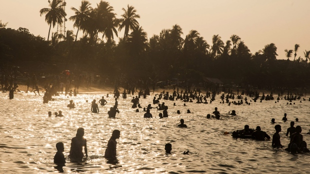 Visitors and tourists are silhouetted as they play in the sea at a beach in Arugam Bay, Sri Lanka, on Saturday, April 15, 2017. In its second review for a $1.5 billion loan, the International Monetary Fund said last month Sri Lanka must remain vigilant in monitoring inflation pressure and stand ready to tighten monetary policy, while recommending exchange rate flexibility. Photographer: Taylor Weidman/Bloomberg