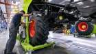 An employee fits wheels to a Lexion 770 combine harvester on the production line at the Claas KGaA factory in Harsewinkel, Germany, on Monday, Aug. 28, 2017. Claas Group, a 104-year-old, family-owned manufacturer of harvesters, threshers and tractors, is hunting for revenue by outfitting machines with sensors, cameras and software to help its products stand out amid slumping demand.