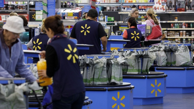 Cashiers ring up shoppers at a Walmart store in Burbank, California.