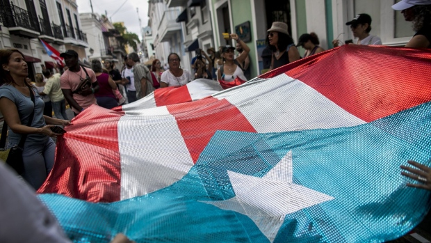People hold the flag of Puerto Rico outside La Fortaleza as they celebrate on the day Governor Ricardo Rossello resigns from office in San Juan, Puerto Rico, on Friday, Aug. 2, 2019. Puerto Rico's House voted in favor of the outgoing governor's chosen successor, Pedro Pierluisi, keeping his nomination alive for now. But confirmation by one of the island's two chambers will do little to ease uncertainty about who will become Puerto Rico's next governor when the current one -- forced out by weeks of massive street protests -- officially steps down at 5 p.m. Friday. Senate President Thomas Rivera Schatz delayed a discussion of Pierluisi's nomination until Monday.