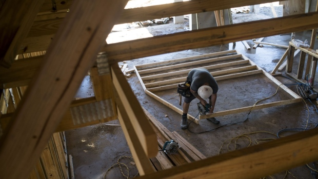 A worker saws a section of lumber inside a home under construction at the M/I Homes Inc. Bougainvillea Place housing development in Ellenton, Florida, U.S., on Thursday, July 6, 2017.
