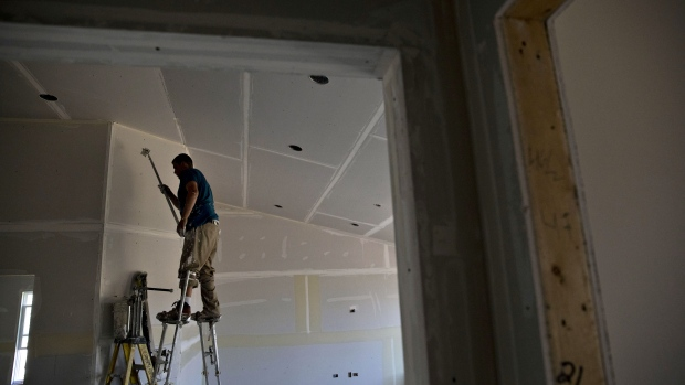 A finisher places tape on drywall seams inside a new home under construction in Plano, Illinois.